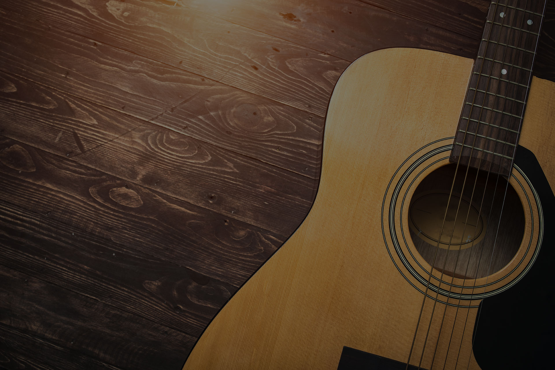 Acoustic guitar resting against a wooden background with copy space